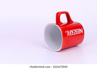 Puchong, Malaysia - February 24, 2019; Promotional red Nescafe mug on white background. Selective focus.