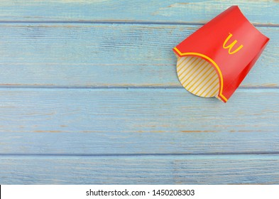 Puchong, Malaysia - July 14, 2019; McDonald's French fries box on wooden background. McDonald's Corporation is the world's largest fast food restaurant.
