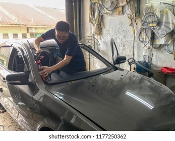 Puchong, Selangor, Malaysia - September 11, 2018; Local workers are in the process of repair new car windshields. Selective focus.