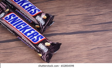 PUCHONG, SELANGOR - MAY 16, 2017: Snickers chocolate bar on wooden background. Snickers bars are produced by Mars Incorporated. Snickers was created by Franklin Clarence Mars in 1930.Selective focus.