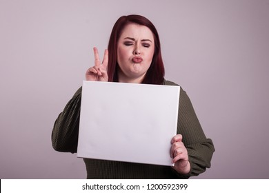 Puckered libs peace sign given by young lady holding a blank poster