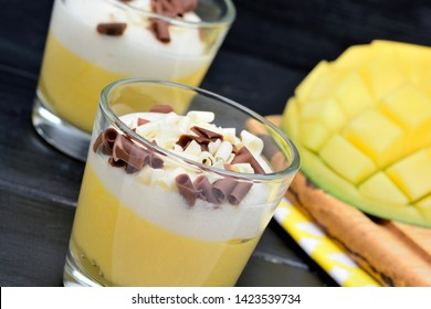 Pudding of mango fruit in a glasses jar and mango cubes on black wooden table