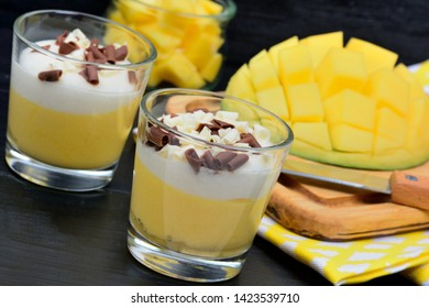 Pudding of mango in a glasses jars on a black wooden table
