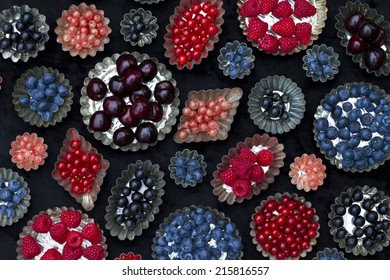 Pudding molds with fresh fruit Strawberry, currant, blackberry, blueberry raspberry, cherry on a black background .