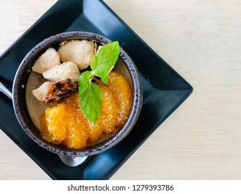 Pudding/Panna Cotta served in a cup on a square saucer, topped with mandarin segments, kinako coated mochi pieces and sesame cracker