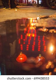 A puddle in a Bejing hutong reflects the red lanterns