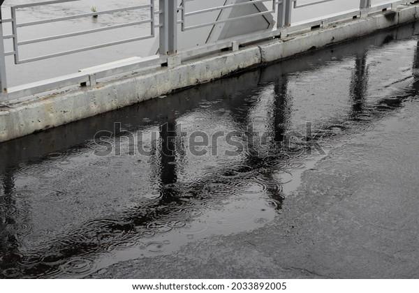 puddle-on-asphalt-along-fence-600w-20338