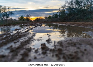 Puddle on a path in the field in which the sunset is reflected, with orange, yellow and blue colors.