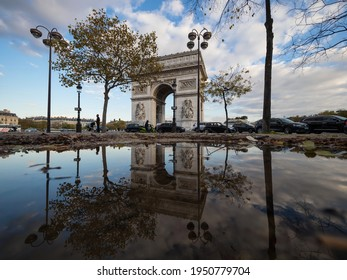 Puddle pond mirror reflection panorama of historic Arc de Triomphe Etoile monument landmark traffic Champs Elysees Paris France Europe