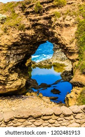 Puddle of quiet water in an arch. Great Ocean Road of Australia. Coastal rocks formed a picturesque arch of sandstone. The concept of exotic, active and photo-tourism