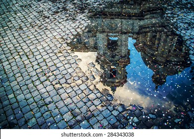 A puddle reflection of the basilica of St Agnes on Piazza Navona in Rome, Italy, covered with colorful confetti after the carnival parade