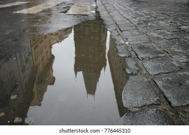 Puddle Reflection and Cobble Street in European Old Town.