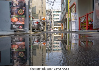 A puddle reflection of Hongdae alleyway. Hongdae is a famous shopping and clubbing district in Seoul, South Korea. Taken on March 17th 2019. Seoul, South Korea