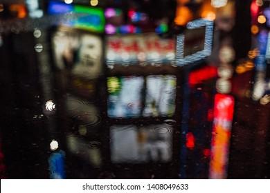 Puddle reflection of Shinjuku red light district Kabukicho. Rainy night in Tokyo, Japan.