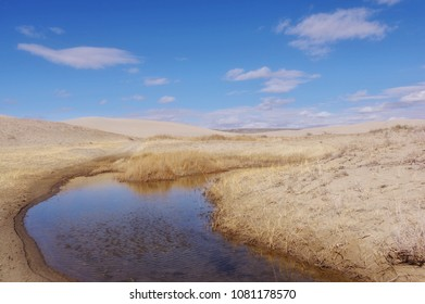 Puddle of water left over from winter snow surrounded by sand dunes. Red desert area of  Wyoming USA. Killpecker sand dunes.