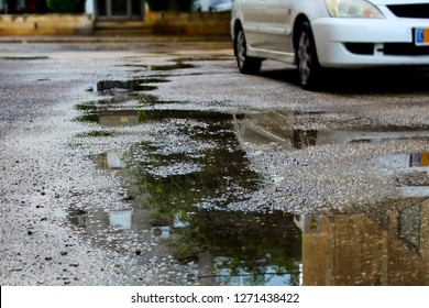 Puddles on the pavement. Winter in Israel, winter weather, after the rain