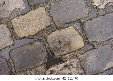 Puddles of water from rain on wet cobblestone road