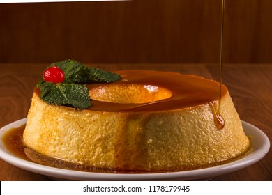 Pudim de leite, a delicious Brazilian flan dessert, with milk and condensed milk, topped with caramel sauce.( It's type of vanilla pudding). Served on white plate on wooden table.