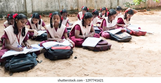 PUDUCHERRY, INDIA - DECEMBER Circa, 2018. Unidentified group children girls friends classmates in government school uniforms sitting on floor, studying with books outdoors.