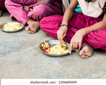 PUDUCHERRY, TAMIL NADU, INDIA - DECEMBER Circa, 2018. Unidentified poor classmates children with uniforms sitting on the floor outdoors, eating with their right hand some rice with masala. Lunch time
