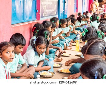 PUDUCHERRY, TAMIL NADU, INDIA - DECEMBER Circa, 2018. Unidentified poor classmates children group with uniforms sitting on the floor outdoors, eating with their right hand some rice with masala. Lunch