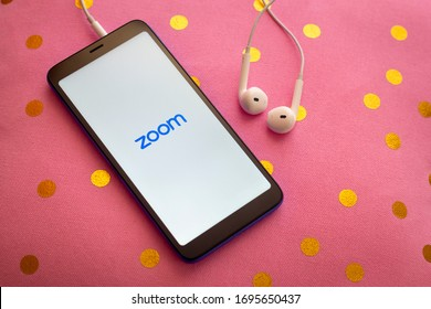 Puebla, Mexico - April 6, 2020: Zoom mobile application on a smartphone with headphones on a pink cushion. Zoom users can choose to record sessions, collaborate on projects, and share or annotate o