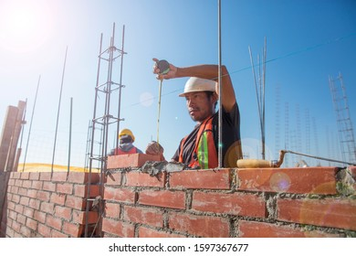 PUEBLA, MEXICO - DECEMBER 24, 2019: Mexican man building a wall of a house with brick and cement. Equipped with helmet and vest