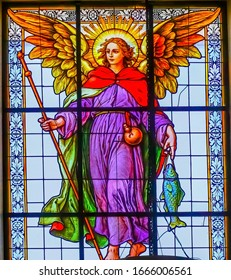 PUEBLA, MEXICO - JANUARY 5, 2019 Colorful Archangel Raphael Stained Glass Basilica Cathedral Puebla Mexico. Built in 15 to 1600s. Raphal is the healing archangle with fish as a symbol