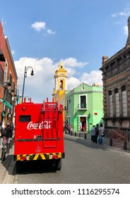 PUEBLA, MEXICO - June 1, 2018: A red truck stands against bright and colorful facades of colonial buildings and houses in historic center of Puebla.