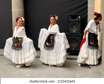 PUEBLA, MEXICO: June 2, 2018: Three Mexican women dressed in traditional white dresses and headdress are dancing during a performance.