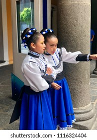 PUEBLA, MEXICO: June 2, 2018: Two Mexican girls dressed in traditional dresses and headdress before going on stage for their dance performance.