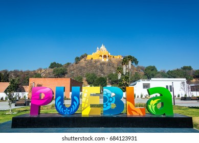 Puebla sign with Our Lady of Remedies on a hill in the background in Cholula, Mexico
