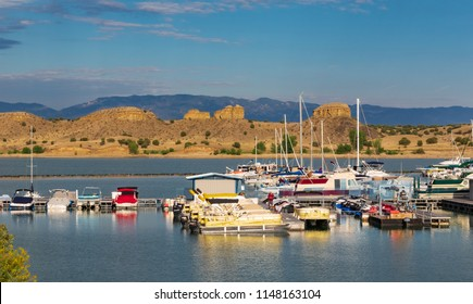 PUEBLO, CO, USA-16 JULY 18: Colorful boats in foreground, rock formations in midground, a distant mountan range, and wispy clouds above--Pueblo State Park.
