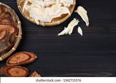 Pueraria mirifica and Butea superba (Kwao khrua), traditional Thai herb that useful for alternative medicine on dark wooden background with copy space. Flat lay
