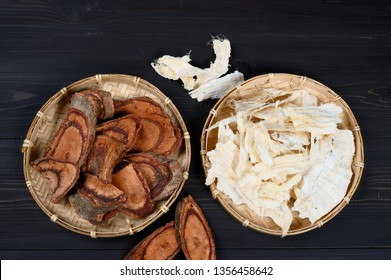 Pueraria mirifica and Butea superba (Kwao khrua), traditional Thai herb that useful for alternative medicine on dark wooden background. Flat lay