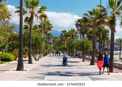 PUERTO BANUS MARBELLA, SPAIN - MAY 2018: People walking along the seafront promenade in the sunny  day. Marbella resort city. Malaga, Costa del Sol. Southern Spain