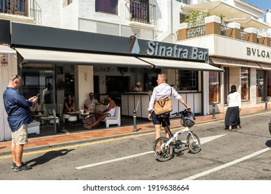 Puerto Banus Marbella Spain October 3 2019. People outside the famous Sinatra bar in Puerto Banus. Man holding his white bicycle on the street. People having a drink in a Spanish bar.
