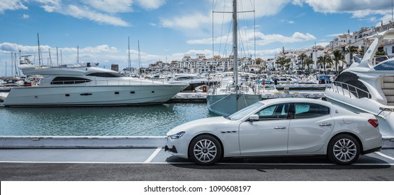 PUERTO BANUS, SPAIN - APRIL 25, 2018: The luxury and jetset harbour and marina in Puerto Banus near the city of Marbella with a white speedboat and a white Maserati sportscar