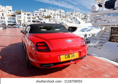 PUERTO BANUS, SPAIN - APRIL 28, 2018:Red Bentley  parked next to luxurious yachts moored in Puerto Banus.