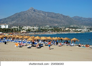 PUERTO BANUS, SPAIN - SEPTEMBER 14, 2009 - Holidaymakers relaxing on the beach, Puerto Banus, Marbella, Costa del Sol, Malaga Province, Andalusia, Spain, Western Europe, September 14, 2009.