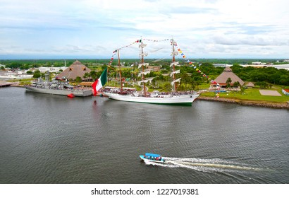 Puerto Chiapas, Mexico.  Mexican Navy ship and Tall ship in Port. Flying a giant Mexican Flag