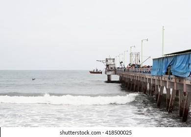 "Puerto de La Libertad / El Salvador - June 30, 2011: Fishermen's hoist a small traditional fishing boat ""Panga"" in order to park it on top of the pier."