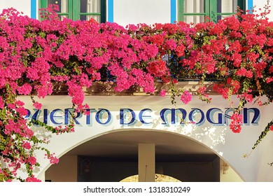 Puerto de Mogan, Gran Canaria, Spain - December 27th, 2018: Detail on a building in harbour with flowers and the name of the popular touristic resort Puerto de Mogan, in Canary islands, Spain.