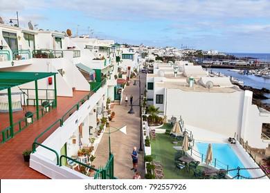 Puerto del Carmen, Lanzarote Island, SPAIN - DECEMBER 1, 2017: Tourists are walking through the Puerto del Carmen town on the coast of Atlantic Ocean, Lanzarote Island, Spain