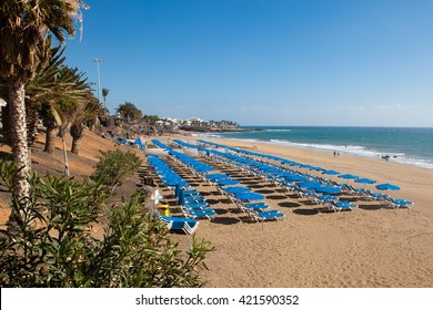 Puerto del Carmen promenade, view of the sunbeds on the beach, Lanzarote, Canary islands