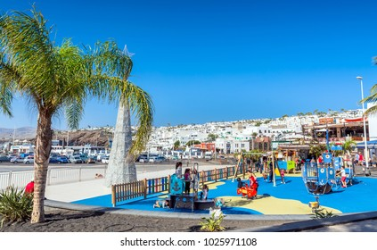Puerto del Carmen, Spain - December 27, 2016: day view of playground and old town with tourists in Puerto del Carmen, Spain. Puerto del Carmen is the main tourist town on the island of Lanzarote.