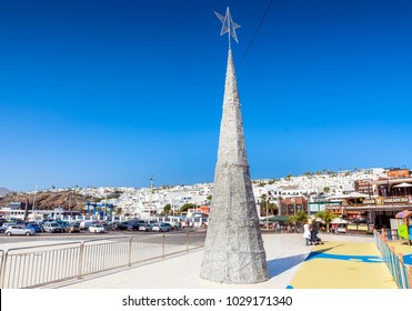 Puerto del Carmen, Spain - December 27, 2016: day view of old town and Christmas tree with tourists in Puerto del Carmen, Spain. Puerto del Carmen is the main tourist town on the island of Lanzarote