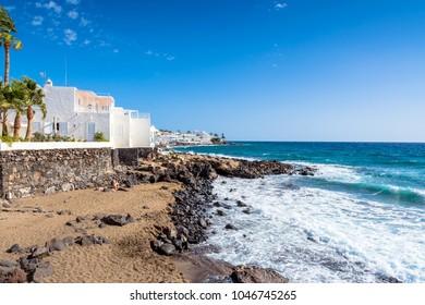 Puerto del Carmen, Spain - December 28, 2016: day view of coastline with tourists in Puerto del Carmen, Spain. Puerto del Carmen is the main tourist town on the island of Lanzarote, Canary Islands.