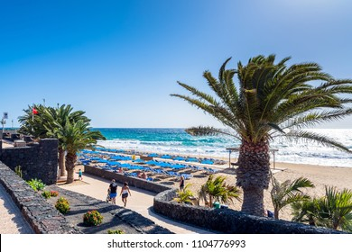 Puerto del Carmen, Spain - December 29, 2016: day view of boardwalk with palms and beach in Puerto del Carmen, Spain. Puerto del Carmen is the main tourist town on the island of Lanzarote.