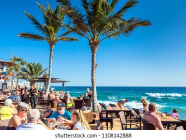 Puerto del Carmen, Spain - December 29, 2016: tourists enjoy drinks and scenery at Cafe La Ola in Puerto del Carmen, Spain. Puerto del Carmen is the main tourist town on the island of Lanzarote.